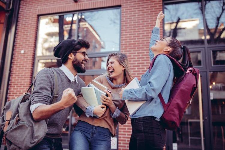 Tres estudiantes celebrando con libros en las manos