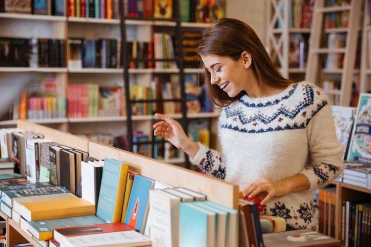 una mujer joven sonriendo escoge un libro en la librería