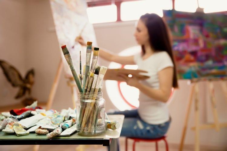 Mujer joven pintando sobre un lienzo en su estudio.